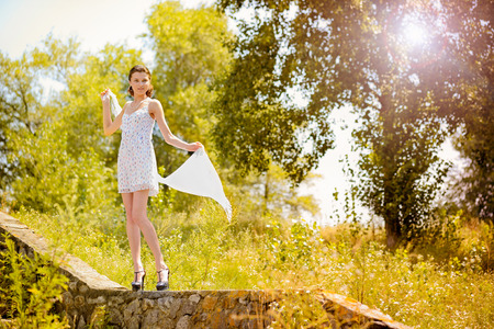 backlite: A young woman with a white dress playing with a white scarf on a little wall in the park with a summer back light Stock Photo