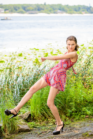 backlite: A young woman with a red dress stand close to the rivers edge where grow herbs and reeds