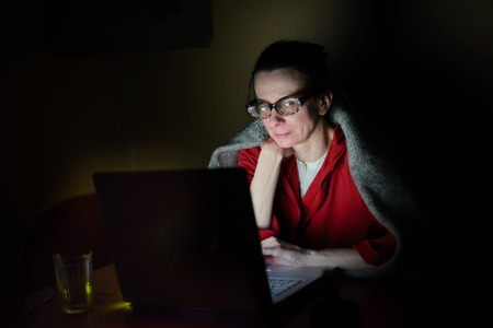 'pull over': A senior woman using a computer in the dark during a cold winter evening