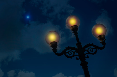 A lantern with three lamps illuminates a starry and cloudy night photo