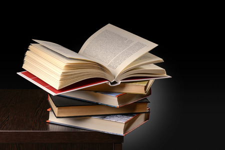 A pile of books with one open on the top, on the desk of a student at evening photo