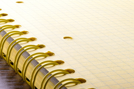 Macro of the spiral of a yellow paper notebook with large deep of field photo