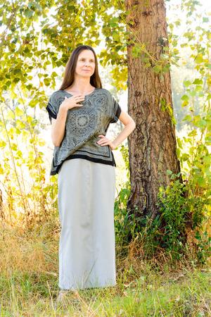 arbol alamo: Una mujer madura elegante con un vestido largo en la sombra de un árbol de álamo agradable en el parque durante un día de verano Foto de archivo