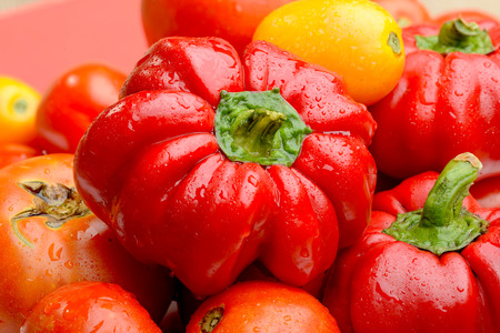 A mix of various fresh tomatoes and bell peppers from the kitchen garden photo