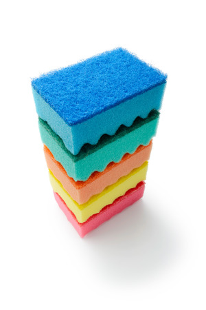 A stack of multicolored kitchen sponges isolated on white background photo
