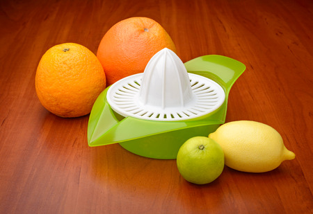 A citrus squeezer with lime, lemon, orange and grapefruit photo