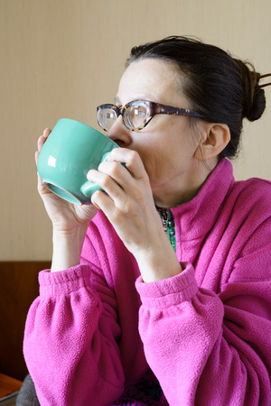 'pull over': A mature woman with glasses wearing a pink pull-over and drinking coffee in a green cup at morning for breakfast