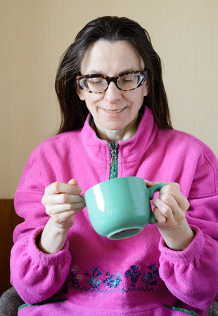 'pull over': A smiling mature woman with glasses wearing a pink pull-over and drinking coffee in a green cup at morning for breakfast Stock Photo