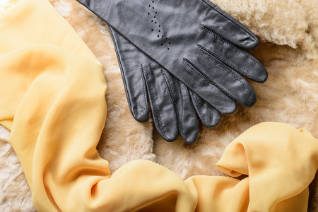 Warm blond sheepskin with black leather gloves and yellow silk scarf photo