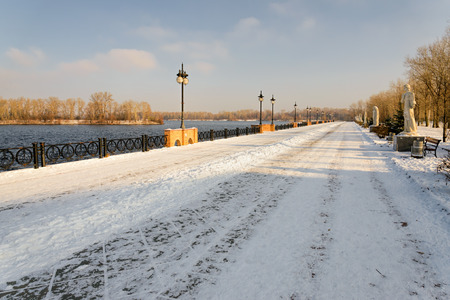Late afternoon promenade in the park, close to the Dnieper river, in winter. The soil is covered by cold snow and ice.