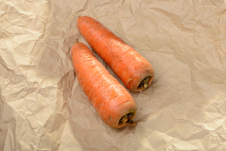 craft paper: Two nice natural carrots on a brown piece of craft paper