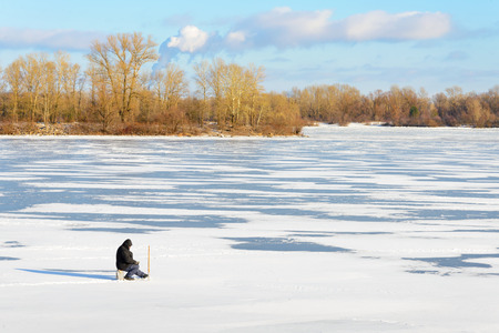 KievUkraine - January 07, 2015 -The Dnieper river is frozen. A sitting fisherman with a rod in hand is waiting under the low winter sun photo