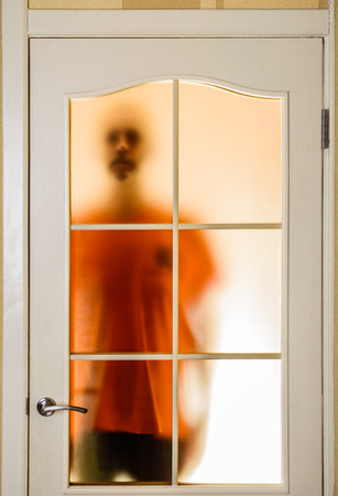 recluse: Silhouette of an unknown man in orange seen through a closed glass door, like a ghost or an alien