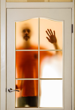 segregated: Silhouette of an unknown man in orange seen through a closed glass door, like a ghost or an alien