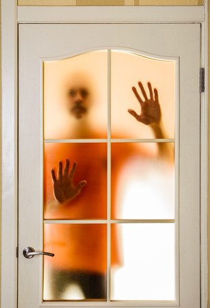 Silhouette of an unknown man in orange seen behind a closed glass door, like a ghost or an alien photo