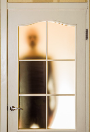 segregated: Silhouette of an unknown man in black seen through a closed glass door, like a ghost or an alien
