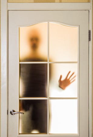 segregated: Silhouette of an unknown man in black  seen through a closed glass door, like a ghost or an alien Stock Photo
