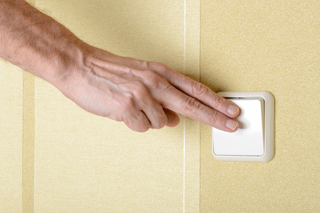 Two fingers switching, in or off, the light with a big square security electric interrupter photo
