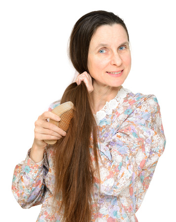 Adult woman combing long brown hair with a wooden comb, isolated on white background