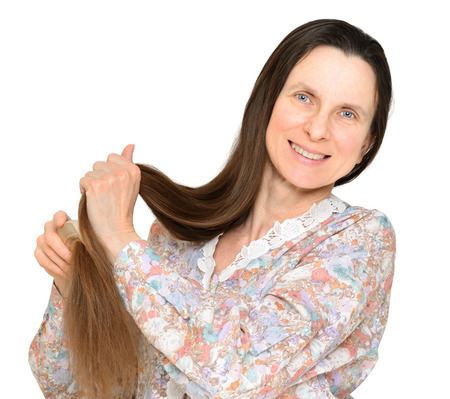 Adult woman combing long brown hair with a wooden comb, isolated on white background photo