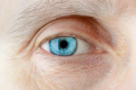 Macro of a hard contact lens on woman's blue eye