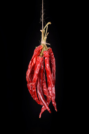 hanged: Hanged dry and sear hot red chili peppers isolated on black background Stock Photo