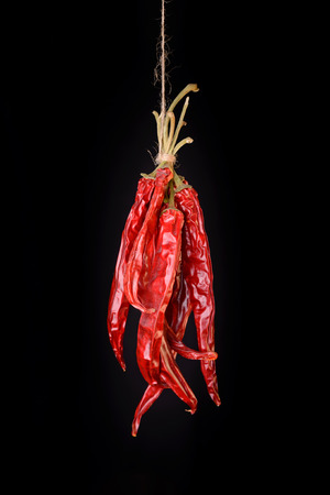 sear: Hanged dry and sear hot red chili peppers isolated on black background Stock Photo