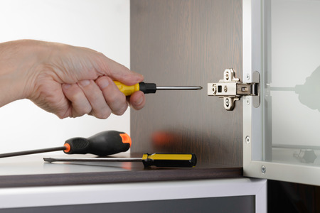 euro screw: A man uses a screwdriver to adjust a concealed hinge fixed on a modern cabinet with a glass door Stock Photo