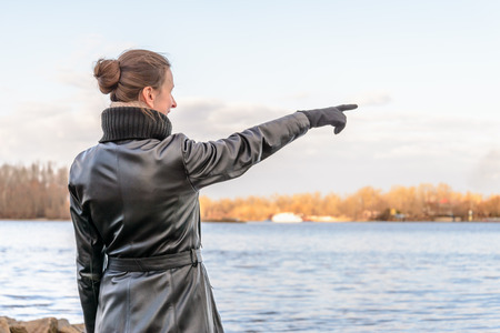 chignon: An adult with a chignon and wearing a black leather coat stays close to the river and point her finger to indicate something interesting on the opposite bank Stock Photo
