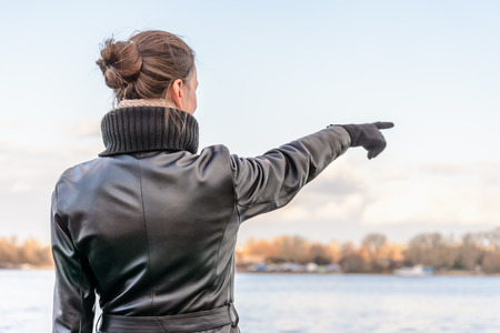 indicate: An adult with a chignon and wearing a black leather coat stays close to the river and point her finger to indicate something interesting on the opposite bank Stock Photo