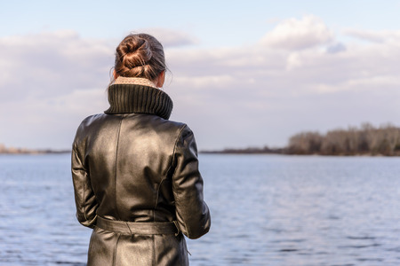 chignon: A woman with a chignon and a black leather coat is watching the landscape close to the lake or the river during a sunny day with big white clouds