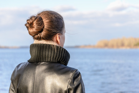 topknot: A woman with a chignon and a black leather coat is watching the landscape close to the lake or the river during a sunny day with big white clouds