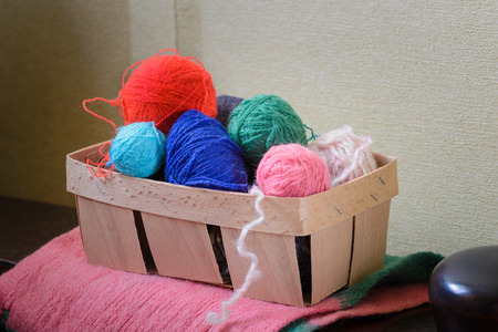 arm chairs: Colorful balls of wool in a crate put on the arm of a wooden armchair Stock Photo