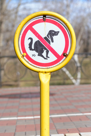 pooping: A sign in a park for no poop with the icon of a dog pooping.