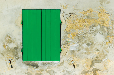 texturized: A closed green shutter and a texturized old wall Stock Photo