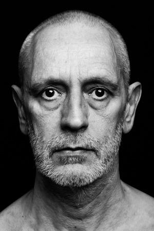 Dramatisch zwart-wit portret van een volwassen man met een droevige uitdrukking op zwarte achtergrond