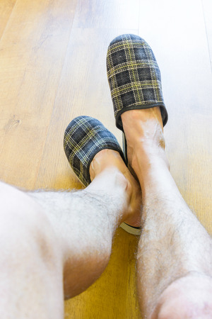 wearing slippers: A man is relaxing while wearing warm slippers and showing hairy legs