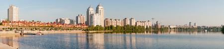dnieper: KievUkraine - June 20, 2010 - The first sun rays caresse the buildings close to the Dnieper river in Kiev, panoramic view Stock Photo