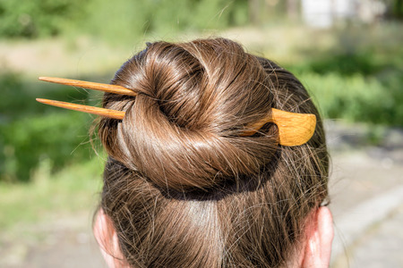chignon: Detail of a chignon with a wooden hairpin to keep the hair attached together