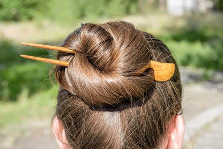 Detalle de un moño con una horquilla de madera para mantener el cabello unido juntos