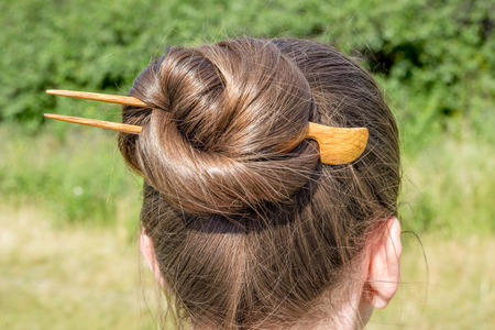 topknot: Detail of a chignon with a wooden hairpin to keep the hair attached together