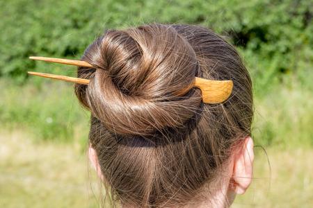 Detail van een chignon met een houten haarspeld om het haar elkaar verbonden te houden Stockfoto