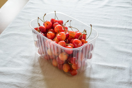 table linen: Morello cherries in a plastic crate on a white table linen