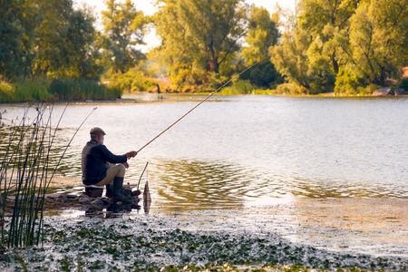 bank activities: Kiev - Ukraine - July 16, 2014: An old fisherman is catching fishes in the Dnieper river in Kiev, in the Obolon district
