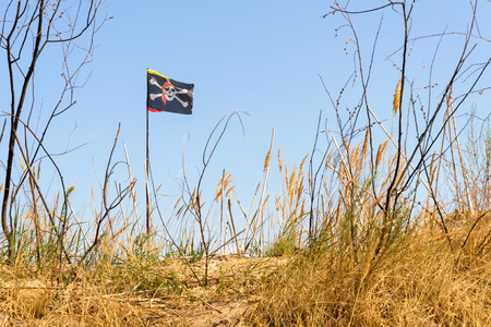 jolly roger: The black Jolly Roger pirate flag flutters in the wind over the hill Stock Photo
