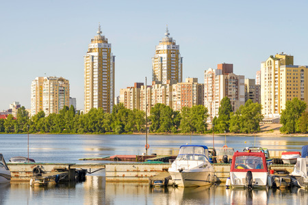 appears: Some boats are parked on the Dnieper River in Kiev, Ukraine. High buildings of the city appears in the background.
