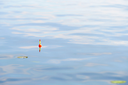 fishing float: A yellow and orange fishing float in blue water