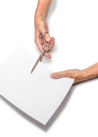 A man is cutting a sheet of white paper using  metallic scissors, on white background