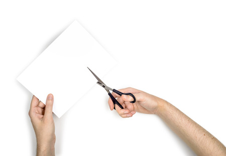 A woman is cutting a sheet of white paper using  metallic scissors, isolated on white background