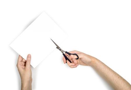 Een vrouw is het snijden van een vel wit papier met metallic schaar, geïsoleerd op een witte achtergrond